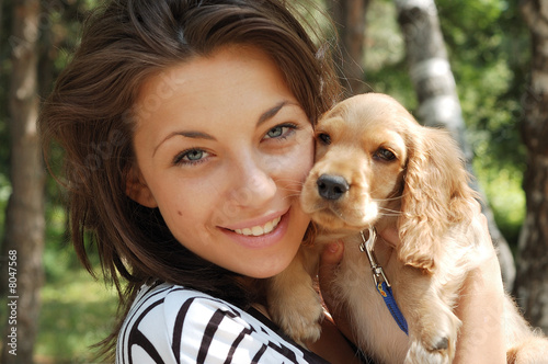 Girl holds her little dog, so cute that it looks like a toy.
