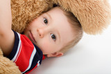 Little boy lye on white bed and embrace toy bear