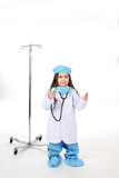 Little girl in medical scrubs with an IV stand and stethoscope