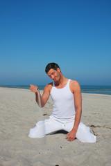 brünetter mann am strand spielt mit sand vergehende zeit