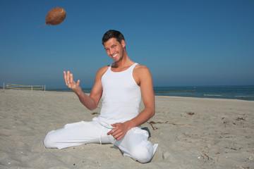 junger lachender mann beim exotischen strandsport