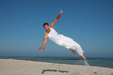 junger mann springt am strand in die luft