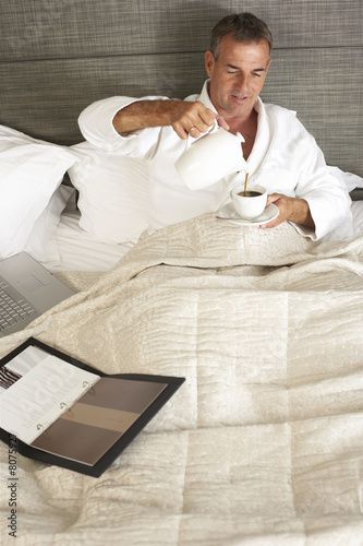 Businessman wearing white bathrobe, sitting in hotel bed, pouring cup of coffee