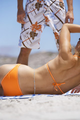 Woman lying on beach in orange bikini, looking up at man, mid-section, rear view, surface level