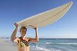 Young woman standing on beach, carrying surfboard on head, smiling, portrait, sea in background