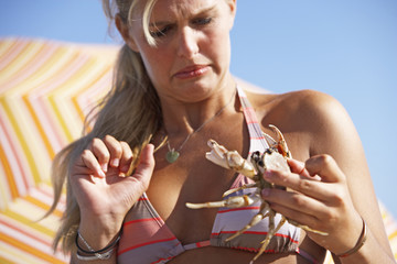 Young woman looking with disgust at crab in hands, close-up