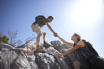Couple climbing rock in bright sunlight, man assisting woman, side view, low angle view