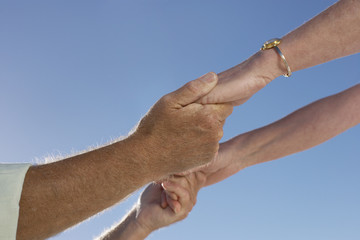 Mature couple holding hands, close-up of hands, side view, low angle view