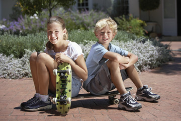 Boy (7-9) and girl (8-10) sitting on brick driveway, holding skateboards, smiling, portrait