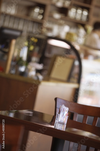 Sugar sachets in glass pot on cafe table, focus on foreground (tilt)