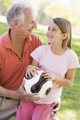 Grandfather and granddaughter outdoors with ball smiling