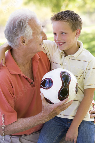 Grandfather and grandson outdoors with ball smiling