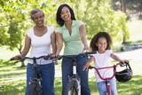 Fototapety Grandmother with adult daughter and grandchild riding bikes
