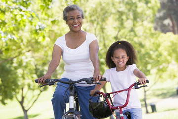 Grandmother and granddaughter on bikes outdoors smiling
