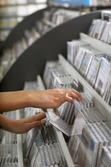 Woman sifting through CDs in record shop, side view, mid-section, close-up