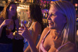 Three young women drinking at a nightclub