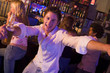Young man in nightclub approaching camera with arms outstretched