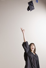 Female graduate throwing cap into the air