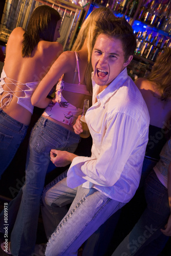 Young man pinching a young woman's bottom in a nightclub