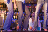Barman gaping at three young women dancing on bar counter
