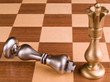 Metal chess pieces on wooden board