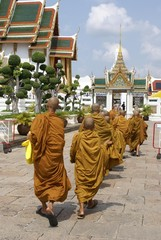 monks walking towards the entrance of a temple