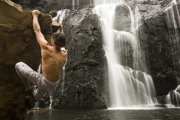 Rock climber at waterfall