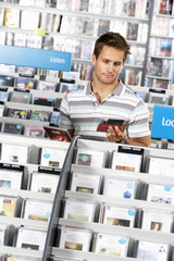 Young man choosing CD in record shop, standing in aisle behind rack, reading album sleeve (tilt)