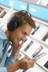Young man wearing headphones, listening to CDs in record shop, smiling, close-up, side view (tilt)
