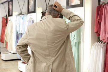 Mature man shopping in clothes shop, scratching head, hand on hip, rear view