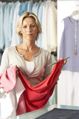 Mature blonde woman shopping in clothes shop, holding red vest top on coathanger, portrait