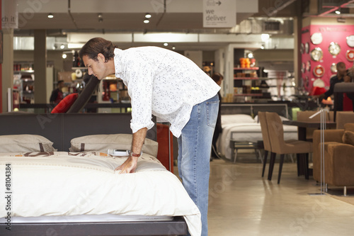 Man testing mattress on new bed in furniture shop, bending down, side view