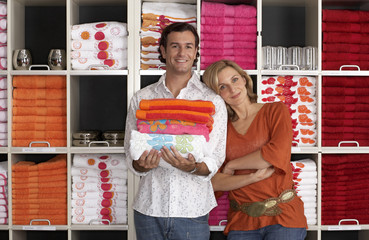 Couple shopping in department store, woman leaning against boyfriend, man holding pile of folded towels, smiling, front view, portrait, shelves in background