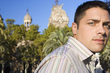 Spain, Barcelona, man standing near local landmark and trees, side view, close-up, portrait