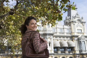 Spain, Barcelona, woman looking over shoulder, smiling, rear view, portrait