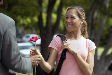 Woman receiving single pink flower from man, laughing