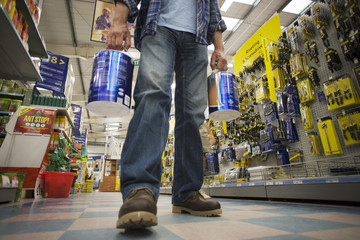 Man shopping in DIY store, standing in aisle, carrying two tins of paint, low section, surface level