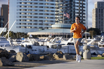 USA, California, San Diego, man jogging in marina, listening to MP3 player strapped to arm