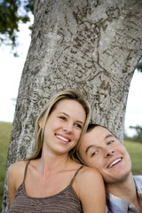 Two young lovers sitting beneath a tree