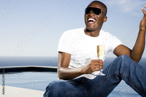 Young man drinking champagne by the pool
