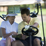 Couple in a golf buggy looking at a plan of the course and score card