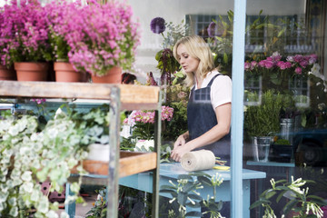Woman florist viewed through the shop front