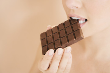 Woman eating a bar of chocolate
