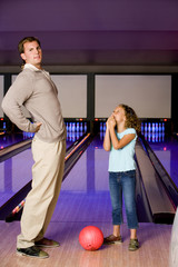 Father and daughter bowling in a bowling alley, father with backache
