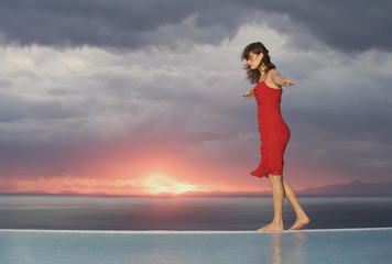 A woman walking along the edge of a pool at sunset