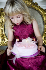 Little girl holding a birthday cake with lit candles