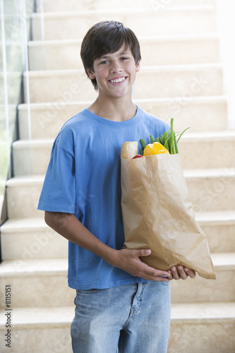 A young boy with a bag of shopping