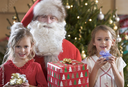 A grandfather dressed as Santa Claus with his grandchildren