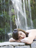 A woman relaxing by a waterfall