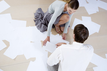 Two business colleagues picking up dropped files and paperwork from the floor